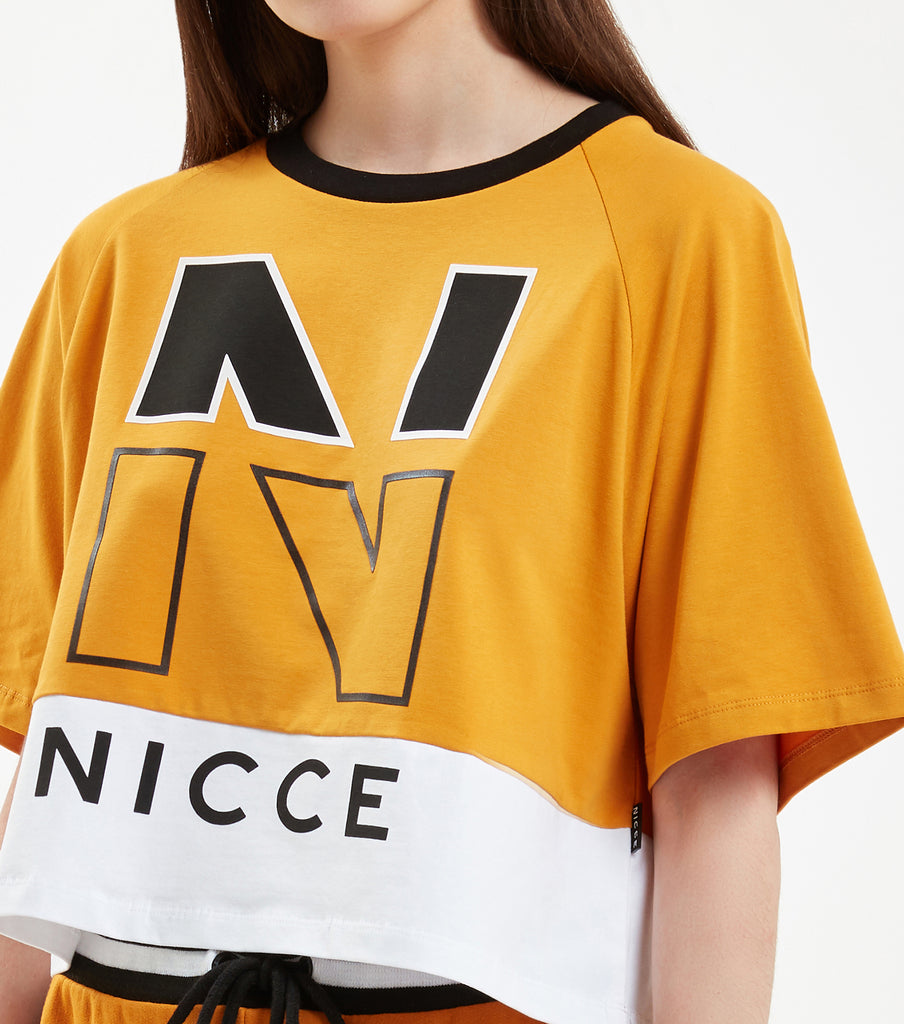 "Fraction cropped raglan t-shirt in golden yellow. Features flat and raised large rubberised ""N"" branding, contrasting colour horizontal panelling and neck finishing. Pair with NICCE Vivid jogger."