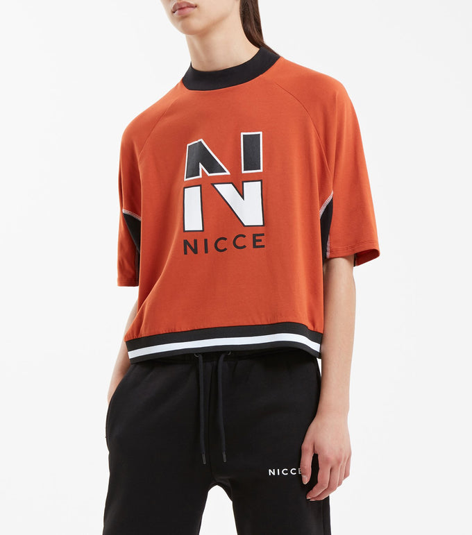 Division t-shirt in burnt orange. Features oversize batwing design, short sleeves, high crew neck rib, contrast under sleeve panelling, sport flat lock threat seam details, contrast high neck rib, two colour stripe rib waistband and black 'N' woven badge. Pair with game leggings.