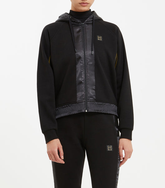 Tidal zip thru hood in black. Features contrast satin panelling with gold seam finishes, hood, ruched waistband elastic, finished with signature small badge branding and signature tab.