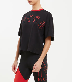 Ambush t-shirt in black. Features drop shoulder boxy fit, Crew Neck, short sleeves, red contrast rib across the neckline and large curved keyline logo, finished with small woven side tab label.