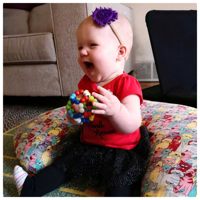 A baby enjoying a wooden grasping ball from her Toy Exchange Club rental toy subscription box