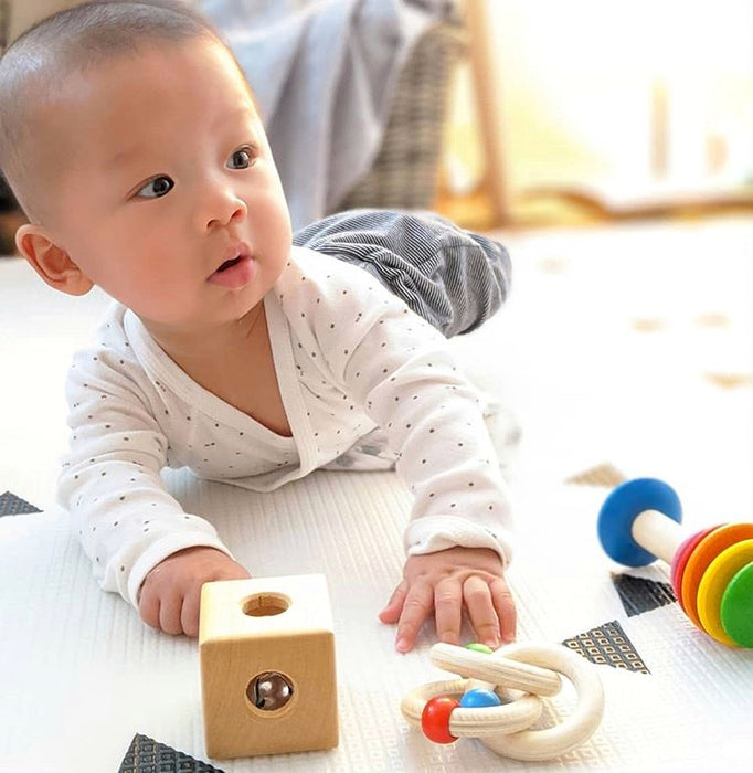 A baby playing with Montessori-inspired toys from his rental toy subscription box