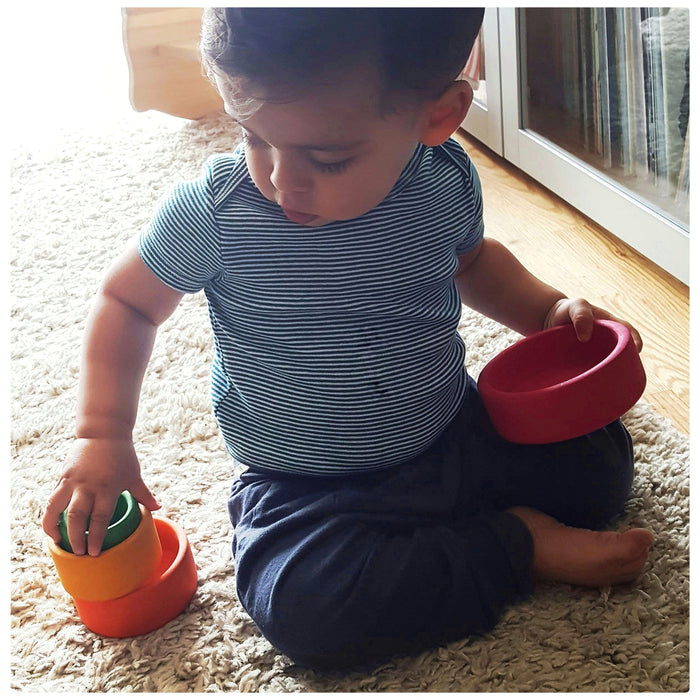 A toddler playing with Grimm's nesting bowls toy from his 15 month old toy subscription box