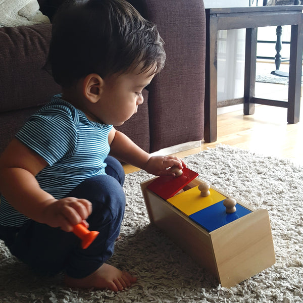A toddler playing with a Montessori box with 3 bins toy