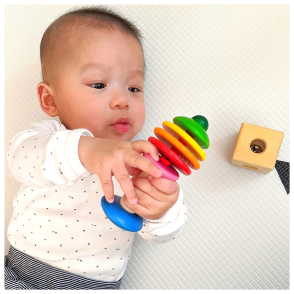 A baby playing with a wooden rattle from his toy rental subscription box