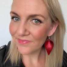 Load image into Gallery viewer, Selfie of Red metallic petal earrings. Faux leather with silver coloured hooks.