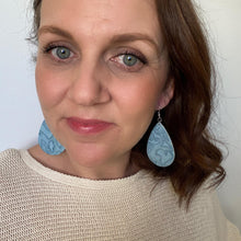 Load image into Gallery viewer, selfie of powder blue embossed teardrop earrings with silver hook