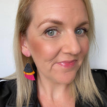 Load image into Gallery viewer, Selfie of colour blocked, triple layer feathered leather earrings featuring a gold coloured hook.