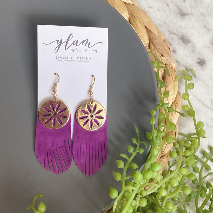 purple fringe leather earrings featuring a gold coloured embellishment and hook