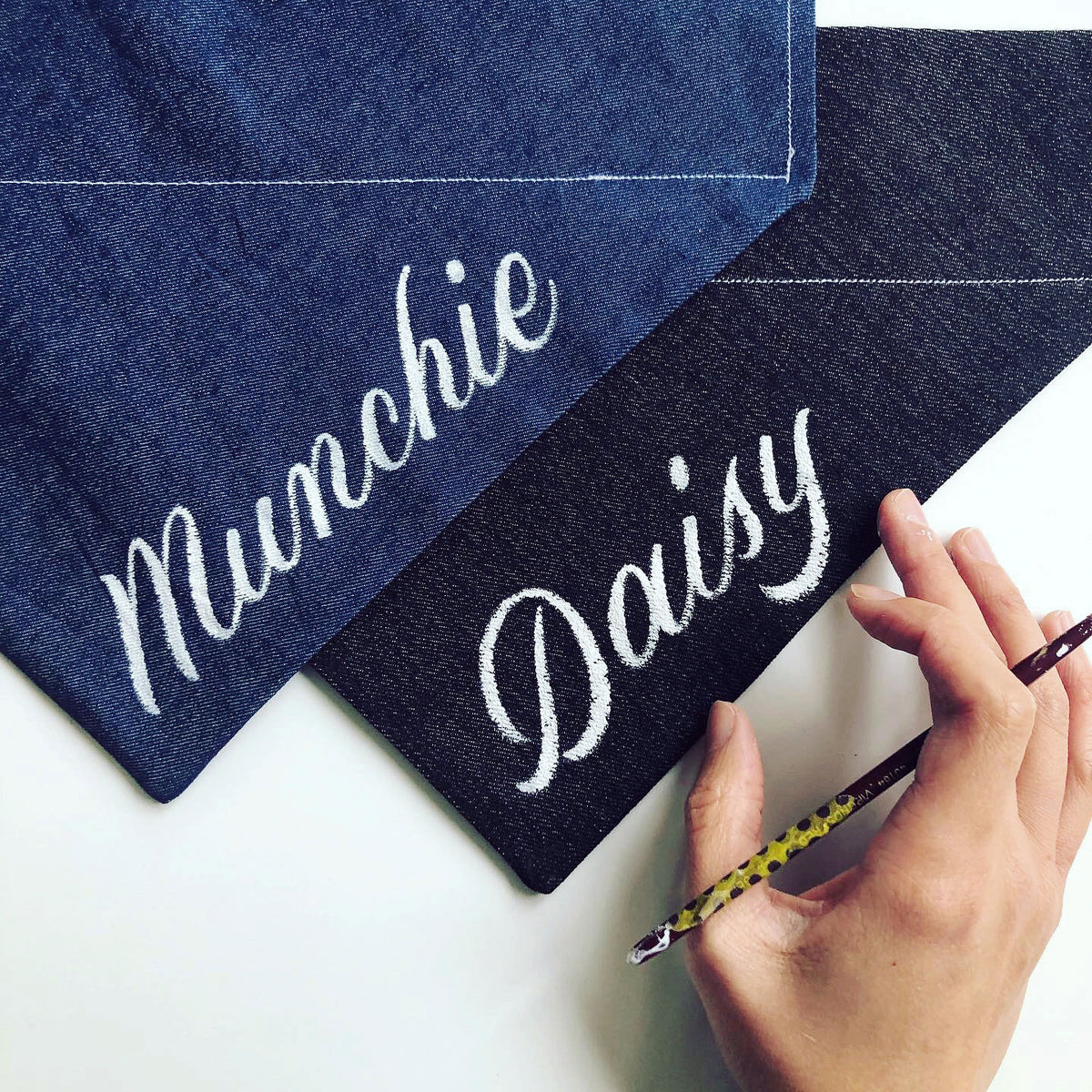 Artist painting cursive script lettering onto personalised denim bandanas for dogs