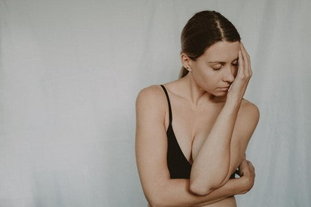 A Woman Wearing a Black Bra and Standing with Eyes Closed and One Arm Across Her Chest and Another Propped Up and Resting on Her Face