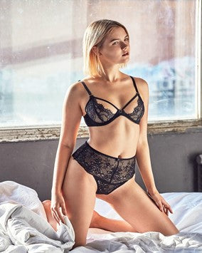 A Caucasian Woman Sitting on Her Knees On A Bed Clad in A Sheer, Black Bra and Panties Set