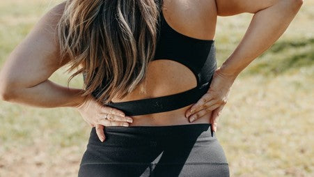 A Faceless Woman in Black Sportswear Holding Her Back with Both Hands
