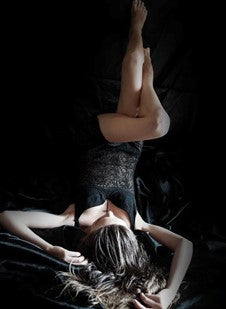 Woman Lying Upside Down with Her Legs Propped Up in Black Sexy Apparel