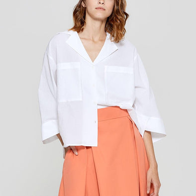 White boxy shirt with chest pockets.