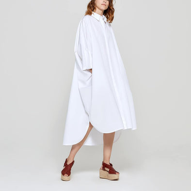 White long shirt dress with medium sleeves.