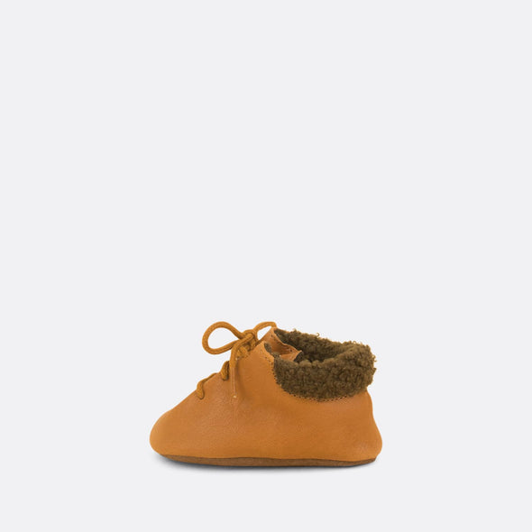 Soft baby booties in cognac leather and detailed with faux fur.