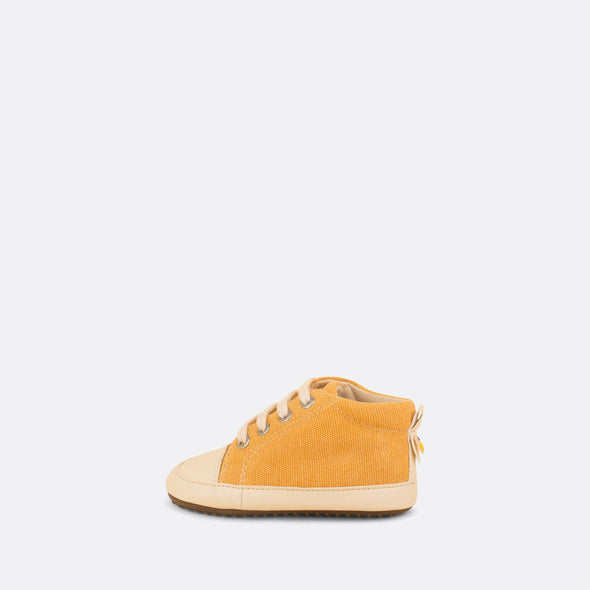 Eco-friendly baby sneakers in yellow recycled cotton with white laces.