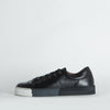 Low top sneakers in black leather with a distinct degrade sole.