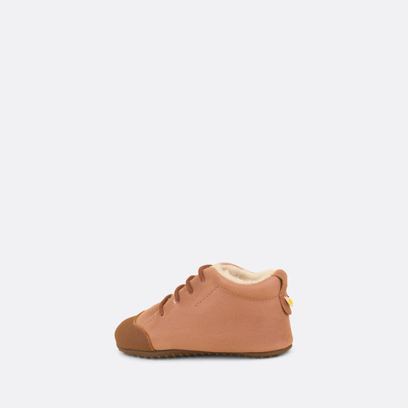 Soft baby chukka in nude leather lined with faux fur.