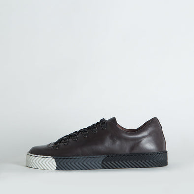 Low top sneakers in deep brown leather with a distinct degrade sole.