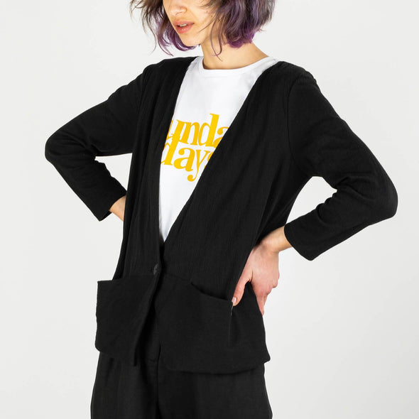 Comfortable black blazer with one single button and discrete pockets.