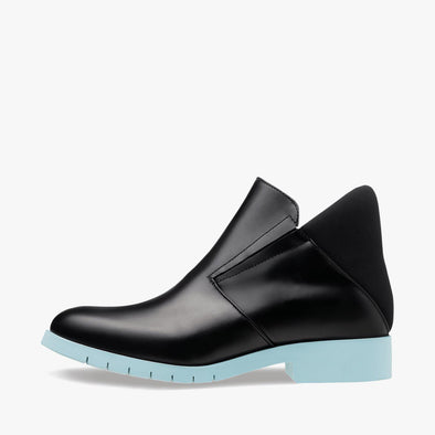 Chelsea boots in black leather with two thin elastic strips in the top and neoprene heel counter and light blue rubber track sole