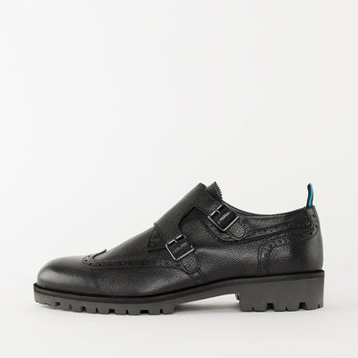 Black double strap monk shoes in black pebbled leather with track sole and wingtip brogue details