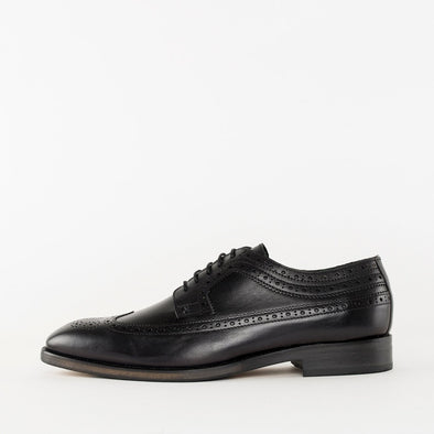 Vintage style derby shoes in black leather with broguing details and wingtip medallion