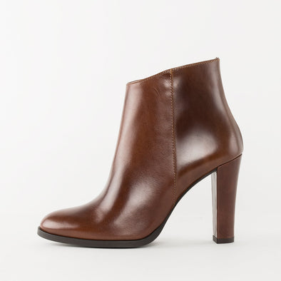 High heeled minimalist ankle boots with an asymmetrical cut in cognac brown polished leather with a pointed toe design and interior zipper