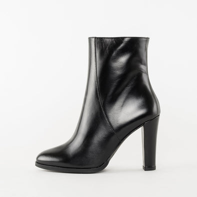 High heeled minimalist ankle boots in black polished leather with a pointed toe design and interior zipper