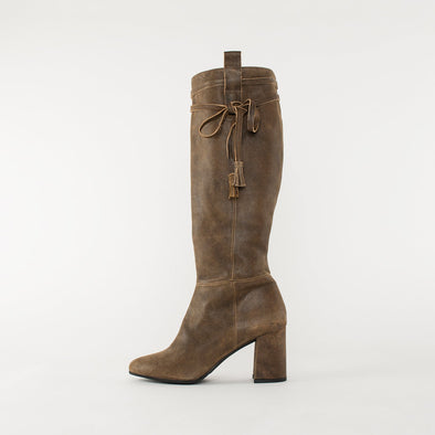 High-heeled knee-high boots in beige waxed suede with a block heel and an embellishing cord with tassels on the knee
