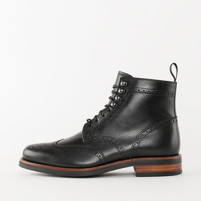 Lace-up boots in black leather with wingtip broguing and chunky build