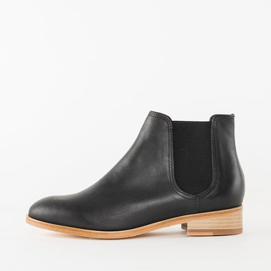 Minimalist chelsea boots in black full-grain leather with contrasting beige sole