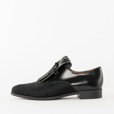 Pointy toed oxford shoes in black patent leather with a textured leather toe cap panel and a fringed tongue
