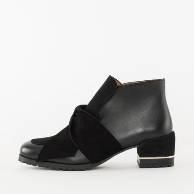 Low heeled ankle boots in black leather with suede panels, a knot across the body of the foot, chunky heel with a thin golden fillet