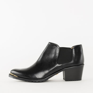 Low cut chelsea booties in black leather with a medium-high block heel and thin golden metallic fillet on the tip