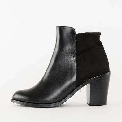 Ankle boots with high block heel, composed of asymmetrical black panels: front in leather and back in suede
