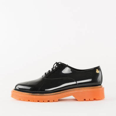 Oxford shoes in black glossy PVC  with mock-brogue medallion tip, contrasting platform sole in bright orange