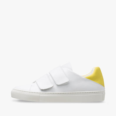 Classic sneaker in white leather with two velcro straps, contrasting yellow heel counter in neoprene and white rubber sole