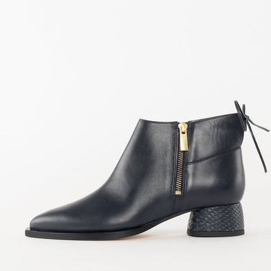 Pointed toe booties in navy blue leather with side zipper and low heel in snake texture