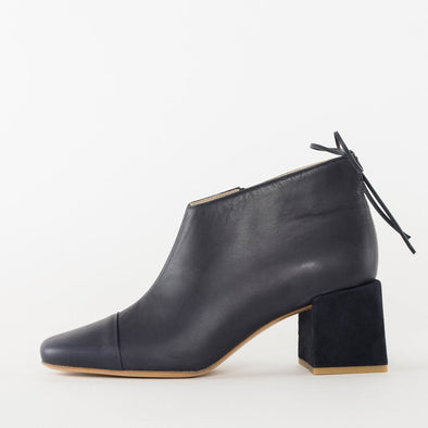 Pointed toe booties in navy blue leather with toe-cap, asymmetrical low-cut ankle with thin tie detail, and contrasting medium-height block heel in suede