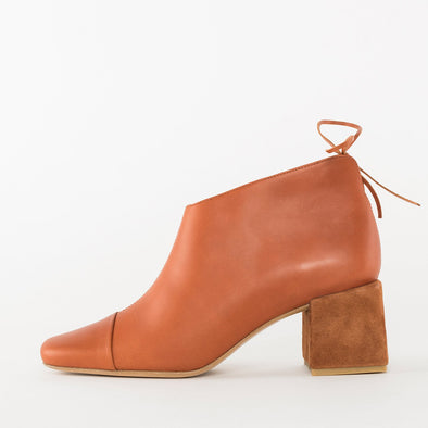 Pointed toe booties in brick orange leather with toe-cap, asymmetrical low-cut ankle with thin tie detail, and contrasting medium-height block heel in suede