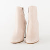 High heeled ankle boots in nude pink leather with a thin adjustable elastic on the ankle, wooden heel with reflective pannel