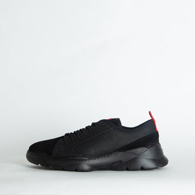 Black runners with a black sole and red details.