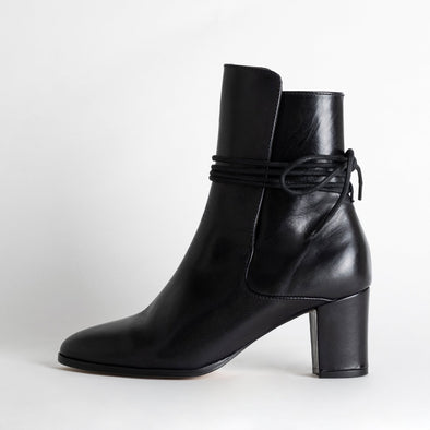 Elegant black heeled ankle boots with thin lace to tie at the back.