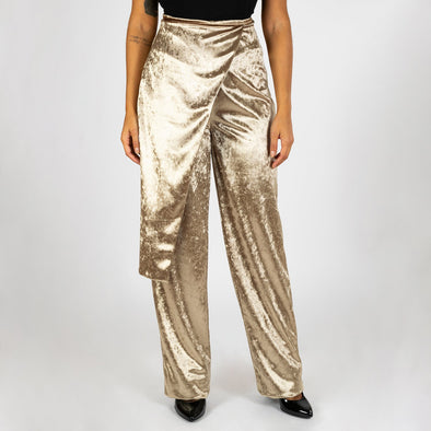 Velvet trousers with asymmetrical detail in a light golden shade.
