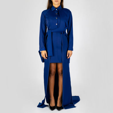 Royal blue trench dress with short front and long back, a wrap waist and golden buttons.