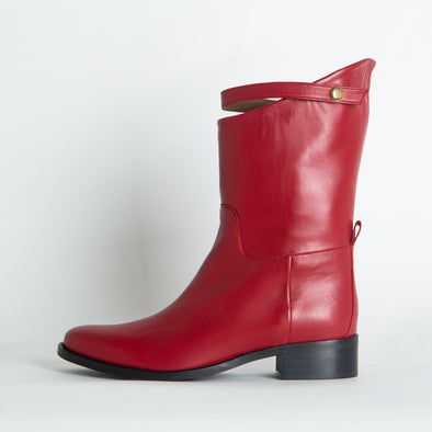 Mid-top red leather boots with a distinct strap.
