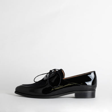 Black flat shoes with laces and patent and textile mix combination.